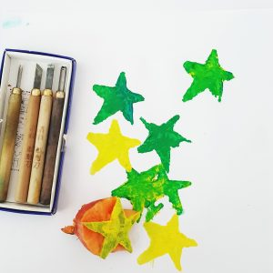 Green and yellow stars stamped from a sweet potatoe stamp. Lino tools picture close by