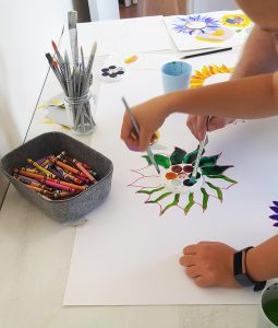 two pairs of hands painting a green sunflower with watercolours . Crayons and paintbrushes sit close by