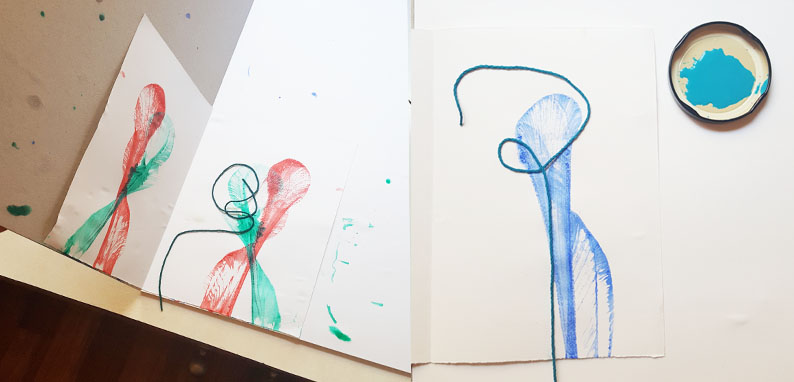 red, green and blue examples of pulled string making ribbon like pictures on white paper